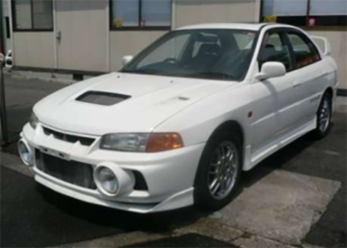 White JDM 1996 Lancer Evolution IV with hallmark fog lights and twin-turbocharged engine