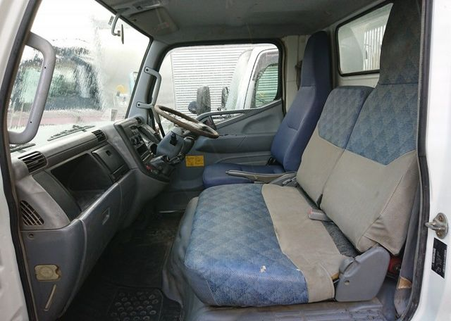 2006 Mitsubishi Canter Dump Truck. Cab interior from passenger's side. Three seat cab
